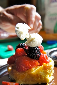 Lemon Zest Bread Pudding with summer berries. lime whipped cream on a bed of chocolate.